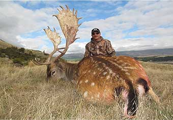 Jeff Fowler with dead animal with large antlers in New Zealand.