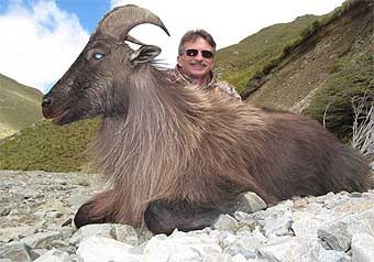 Jeff Fowler with horned dead animal in New Zealand.